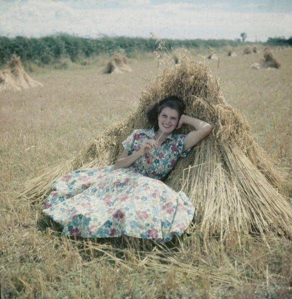 Smiling country girl in floral print summer frock leans back leisurely in a corn field after the harvest