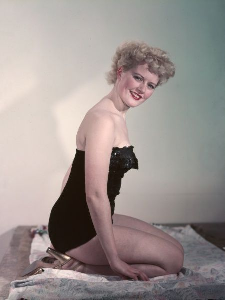 Blonde fifties pin-up wearing a black, off-the-shoulder garment (bathing costume or underwear ?) & gold slingback sandals, kneels on a floral print rug