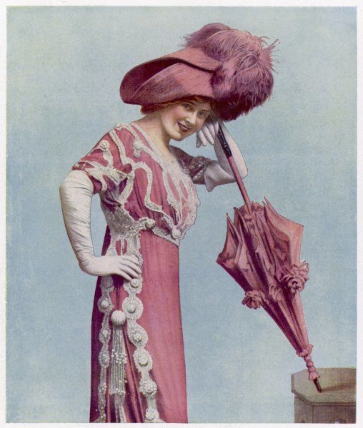 Miss Hazel Dawn in a pretty pink Directoire style gown with a high waist & narrow skirt with a panel in the side to aid mobility. Her picture hat has a large ostrich plume