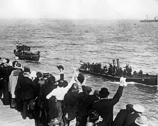 Pinnaces landing sailors at Ostend during the early part of the First World War. Civilians wave to them from above. Date: 1914