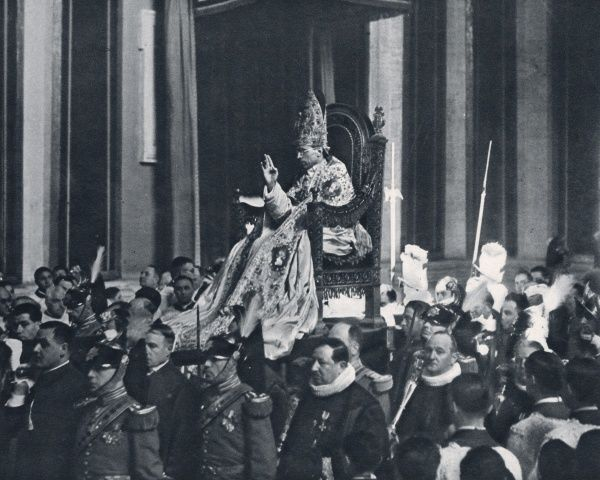 The new Pope, Pius XII, is carried through St Peters, seated on the Sedia Gestatoria, wearing a jewelled mitre, and raising his hand in benediction