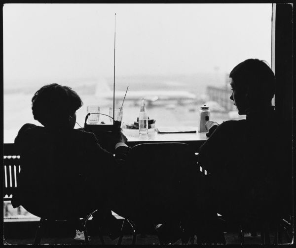 Silhouettes of two plane spotters at London Gatwick Airport, England