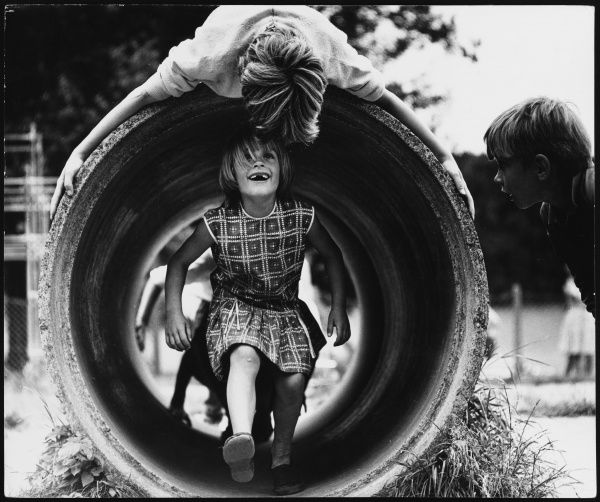 Children playing in a concrete playground tunnel