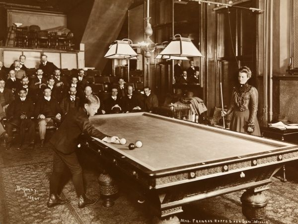 Mrs. Frances Hoppe & Her Son Willie. Mrs. Frances Hoppe playing billiards with her son Willie (William F. Hoppe) in a billiard room with seated spectators watching