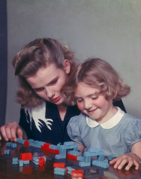 A little blond girl and her Mother play with Lego building blocks, possibly building a train which is travelling under two little Lego bridges? Photograph by Heinz Zinram
