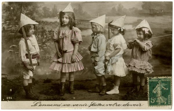 French children with makeshift helmets and swords, playing at soldiers Date: Twentieth century