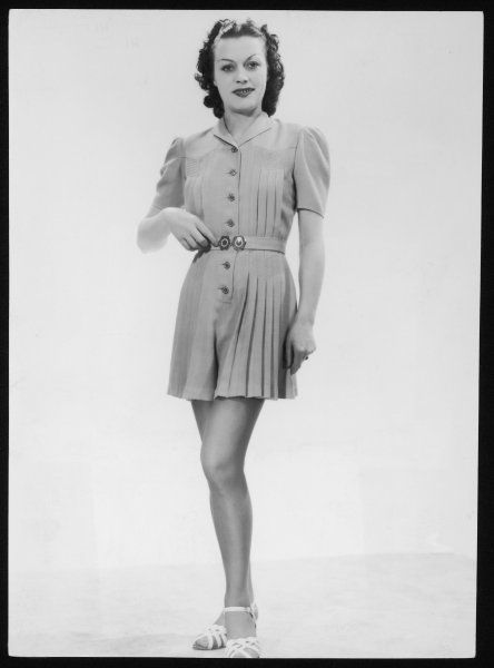 A one-piece play-suit with pleats stitched on the corsage and at the waist