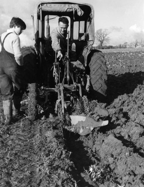 A farmer gives ploughing instruction to a new farm hand. Date: 1960s