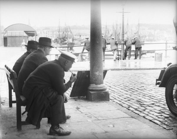 Men relaxing around the harbour in the Barbican area of Plymouth, Devon, England