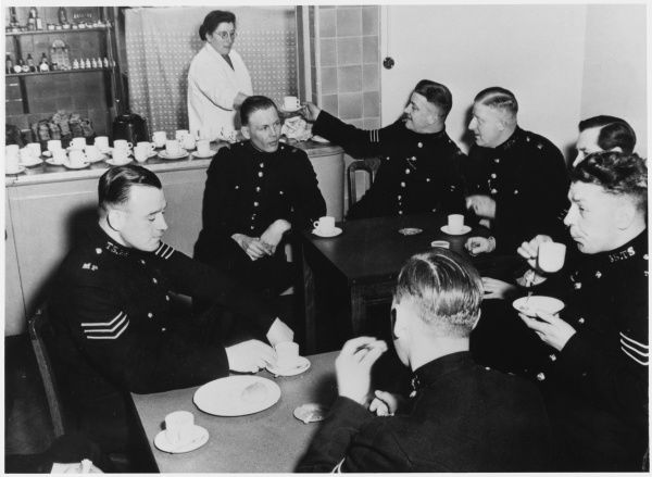 Metropolitan Police officers in their canteen drinking cups of tea