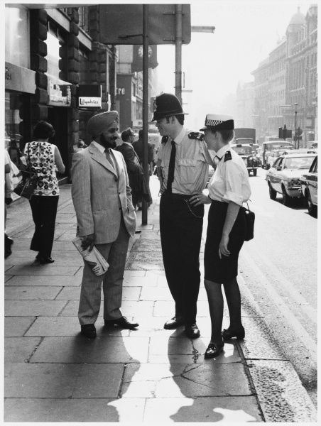 Police officers talking to an Asian man in the street. Metropolitan Police