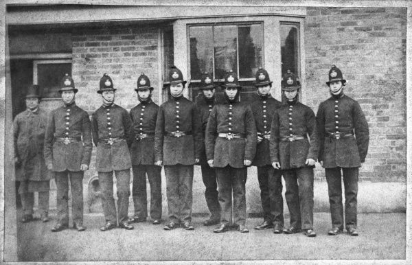 Group of police officers wearing combed back helmets, in use between 1864 and 1870. Metropolitan Police