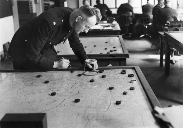 Police map operator plotting the position of various police units on a large table map of london. Exact positions are found using the table magnifying glass. Different counters refer to different types of units or incidents of note
