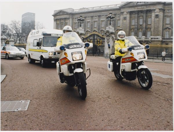 Metropolitan Police motorcyclists esccorting an ambulance past Buckingham Palace in London