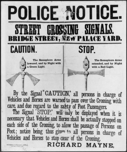 A Police Notice showing Street Crossing Signals in Bridge Street, New Palace Yard, London, close to Parliament and the Met Police headquarters. Semaphore arms and a light for night time indicate Caution and Stop, to allow safe crossing for pedestrians