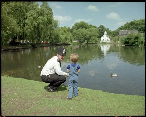 Police officer talking to little boy by lake. Metropolitan Police