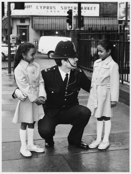 Police officer talking to two little girls in the street. Metropolitan Police