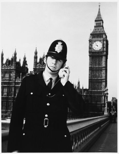Police Officer on the walkie talkie radio on Westminster Bridge by Big Ben and the Houses of Parliament, London Metropolitan Police