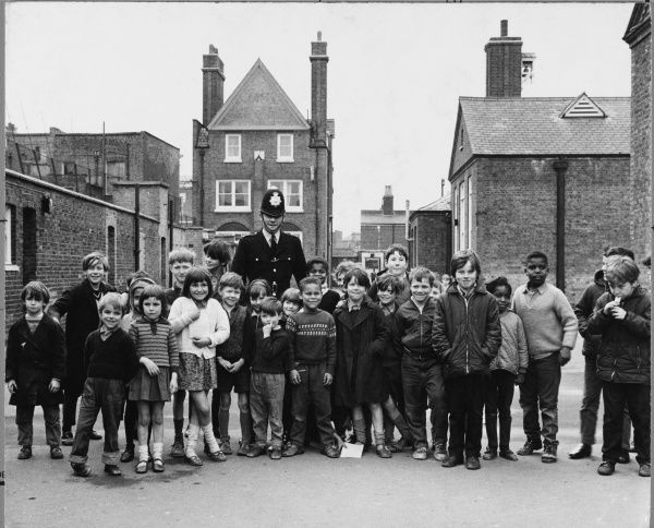 Police officer with group of schoolchildren in a school playground. Metropolitan Police