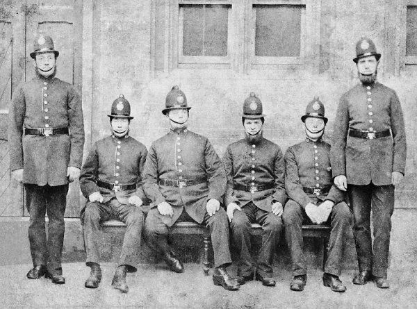 Group of police officers wearing the combed back helmet, in use between 1864 and 1870