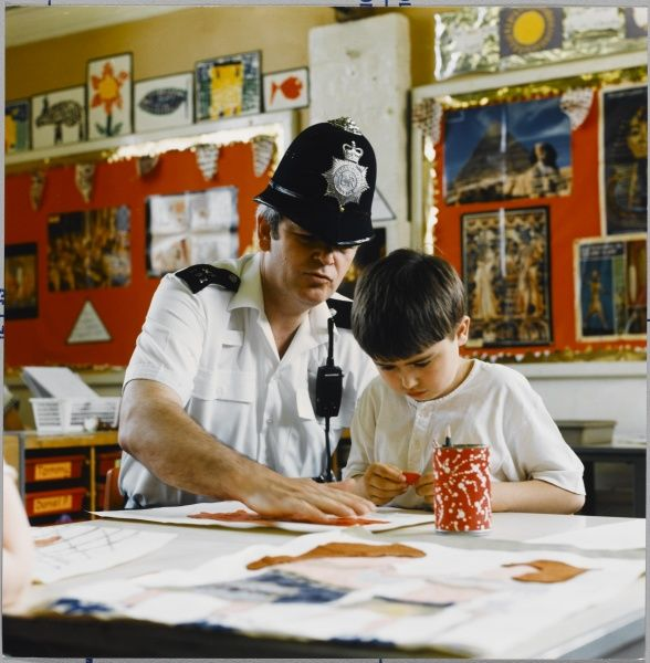 A Metropolitan Police officer helps a boy with his art lesson in school