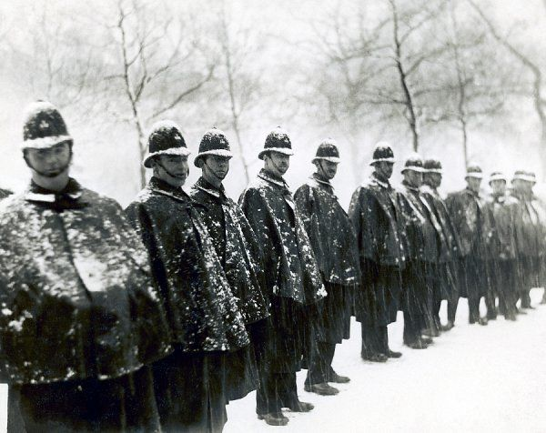 A group of Metropolitan Police Officers stand in a line in the snow