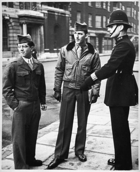 Metropolitan police officer talking to two American servicemen, G.I. soldiers in London