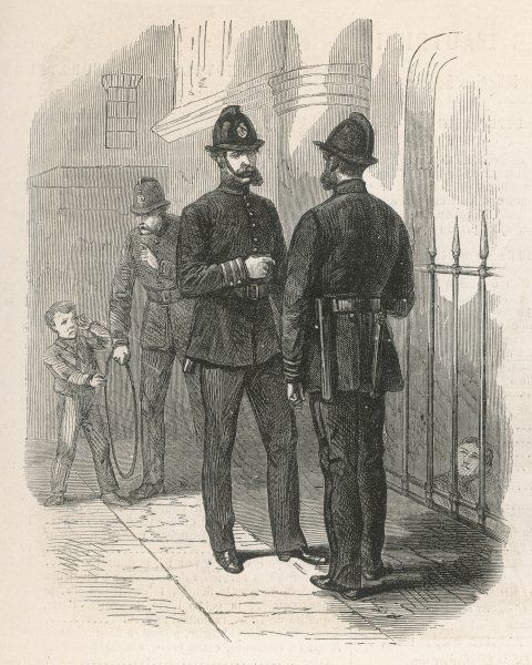 Two London policeman stand chatting in their standard uniform, while their colleagues ticks off a small boy with a wooden hoop, who has been making mischief