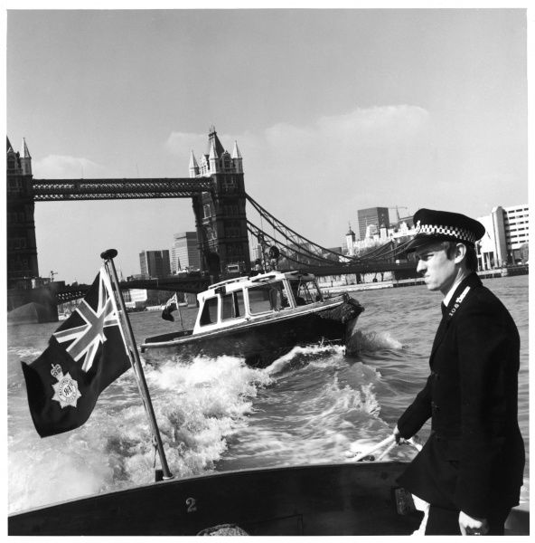Metropolitan Police officer on a launch of the Thames Division patrolling on the River Thames, London