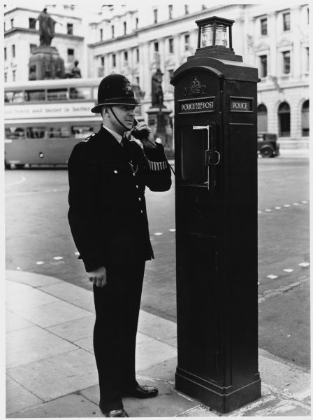 A police officer on the beat south of Pall Mall, central London, reports back to the station using a police call box
