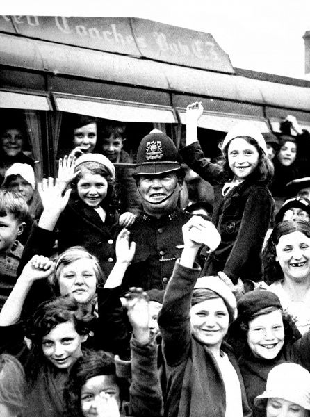 Photograph showing a policeman surrounded by children from the East End of London, prior to their setting off on a day trip to the countryside, at West India Docks, London, 1936