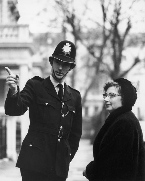 A friendly young policeman points a middle-aged lady in the right direction