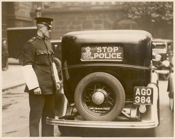 A policeman wearing white armbands used when directing traffic, stands next to a police car with a 'Stop Police' sign on the back