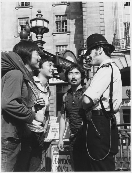 Policeman talking to tourists by the London Underground Metropolitan Police