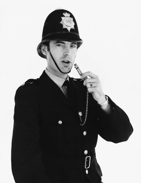 A policeman gets ready to blow his whistle