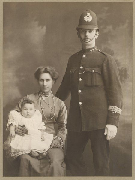 A proud British policeman, in his uniform, stands beside his wife and baby