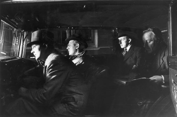 Non-uniformed police officers and detectives on a stake-out sit in a large unmarked car, watching and waiting
