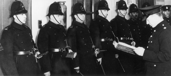 A line of policemen standing in their uniforms, with notebooks, whistles and truncheons at the ready, in a station parade room, before going on duty. Their commanding officer gives them a briefing