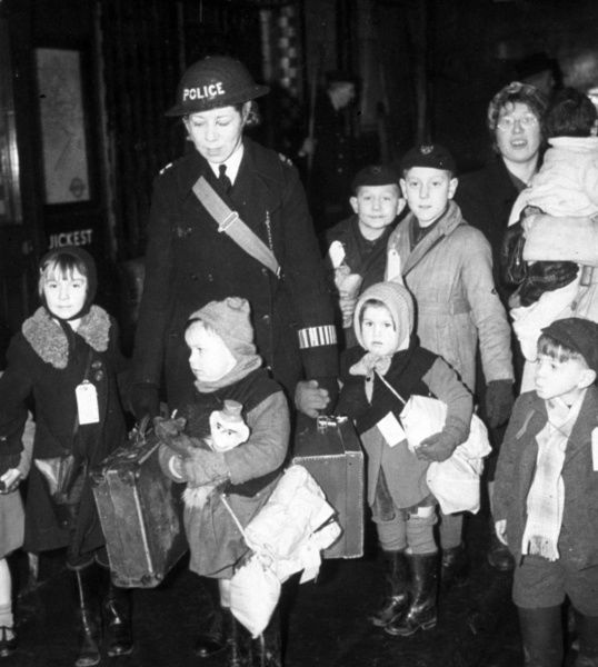 A policewoman helping evacuee children find their train out of London during the Second World War