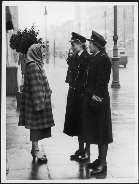 A woman asks two policewomen for assistance