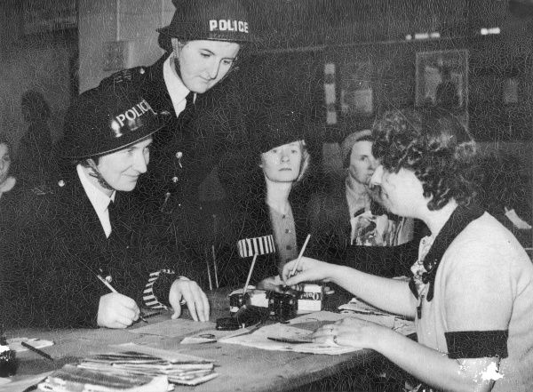 Two Met Police women registering for war work at a labour exchange in London