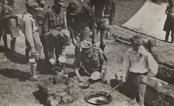 Polish Scouts crowding around to receive food cooked and served by other scouts