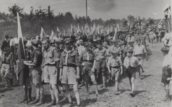 Polish Scouts march at a Jamboree holding the Polish flag. 1930s