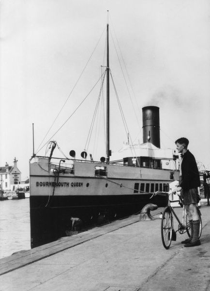 A cyclist stands with his bicycle on the quayside of Poole Harbour, Dorset, England, where the steamship 'Bournemouth Queen' is moored. Date: 1940s