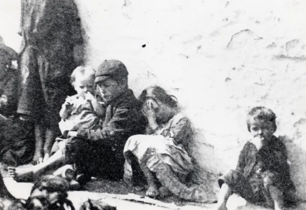 A group of poor children with bare feet photographed on the street in a South Wales mining district