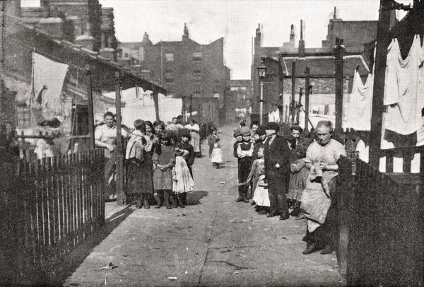 A poor street, location unknown, in the East End of London. Local residents, mostly children, look suspiciously towards the camera. Washing is hanging up to dry in each back yard