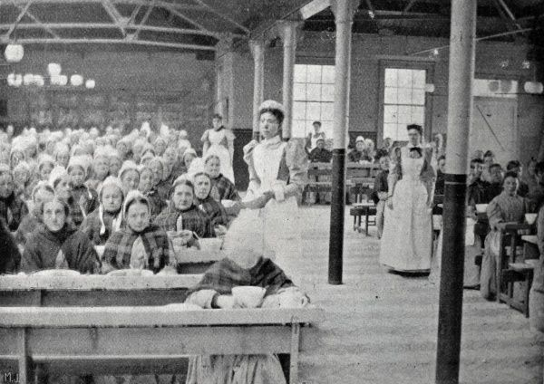 Rows of women in the inmates' dining hall at the Poplar Poor Law Union workhouse in the East End of London. Date: 1903