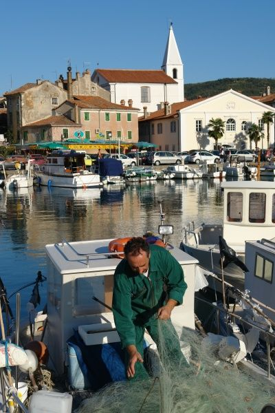 View of the port and town of Izola, Slovenia, with a fisherman in the foreground