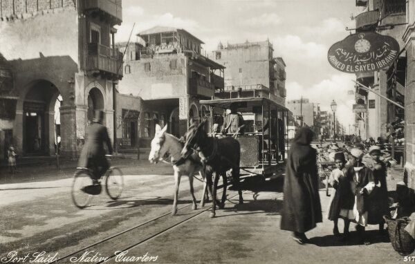 Street scene in the 'Native Quarter' of Port Said, Egypt with a double mule-pulled tram, a cyclist and group of schoolchildren