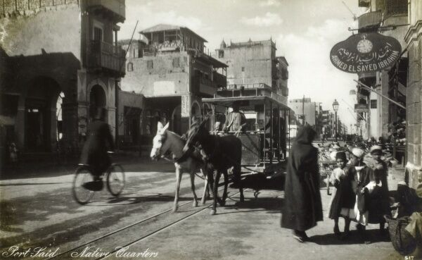 Port Said, Egypt - Street Scene with mule-pulled tram and a watchmaker's shop. Date: 1909
